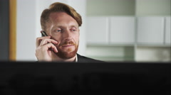 Red-haired man sitting at a computer and calling on the phone - stock footage