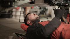 Young mechanic in red overalls repairs a car while under her Stock Footage