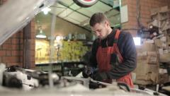 Young mechanic in red overalls engaged manual assembly machines - stock footage