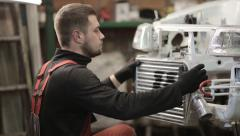 Young mechanic in red overalls engaged manual assembly machines Stock Footage