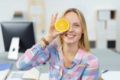 Playful young woman holding an orange to her eye - stock photo