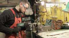 Mechanic in red overalls working hand drill Stock Footage