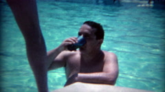 1965: Man caught drinking in the pool by sexy legged cocktail waitress.  Stock Footage
