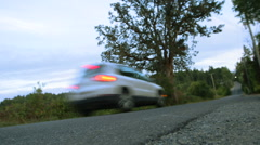 A back view as a car speeds across the road Stock Footage