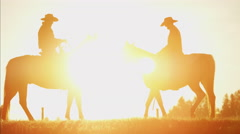 Silhouette of cowboy riders in wilderness area of Canada at sunrise Stock Footage