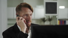 Red-haired man sitting at a computer and calling on the phone Stock Footage