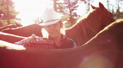 Canadian Female Cowgirl grooming horse on Dude Ranch - stock footage