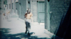1954: Boys dress in orange practicing rollerskating on city streets. Stock Footage