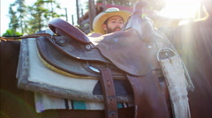 American Cowboy in Corral saddling horse on Dude Ranch - stock footage