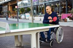 Disabled man enjoying a game of ping pong in his wheelchair Kuvituskuvat