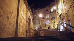 People walking down staircase at night in old portuguese city Coimbra Stock Footage