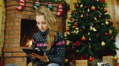 Woman with a tablet near the fireplace Stock Footage