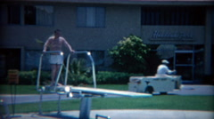 1965: Fat man jumping off hotel pool diving board making big splash. LAS VEGAS Stock Footage