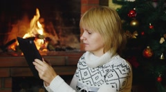Woman works with a tablet near the fireplace and Christmas tree Stock Footage