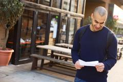 Young man reading a letter in the street Stock Photos
