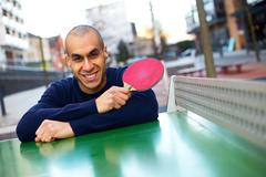 table tennis player posing holding a racket - stock photo
