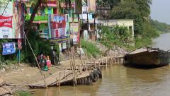 People walk by a dock on the banks of the River Ganges, India Stock Footage