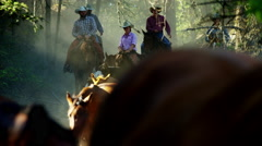 Horses running in roundup on Dude Ranch with cowboy and cowgirl riders - stock footage