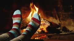 The girl warms his feet by the fireplace - stock footage
