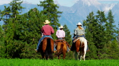 Cowboys and Cowgirls galloping on Kootenay Mountain Range - stock footage