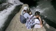 Stock Video Footage of Hikers seated on top of waterfall