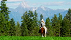 Cowgirl galloping across Kootenay Mountain Range - stock footage