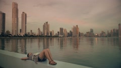 Woman relaxing on shore of big city Stock Footage