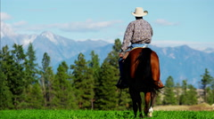 Cowboy galloping across grassland on Kootenay Mountain Range - stock footage