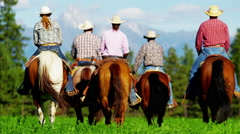 Cowboys and Cowgirls galloping Kootenay Mountain Range - stock footage