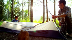 Caucasian American male parent teaching boy build tent on vacation outdoors - stock footage