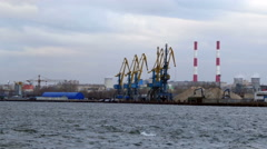 Cranes and pipes near the shore of the river Stock Footage