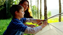 Caucasian female parent teaching son assemble tent on holiday outdoors - stock footage