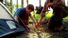 Caucasian male parent son building tent in woodland on holiday outdoors - stock footage