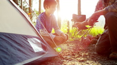American Caucasian father and son erecting tent in forest on holiday outdoor - stock footage