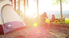 American Caucasian parent and children camping in woodland on vacation outdoors - stock footage