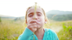 Caucasian American female kid blowing dandelion on vacation outdoors - stock footage