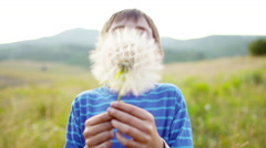 Happy young boy playing in field and blowing dandelion outdoor - stock footage