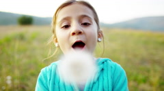Happy American girl blowing dandelion in meadow on vacation outdoors - stock footage