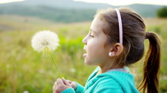 Caucasian American female kid blowing dandelion on holiday outdoors - stock footage