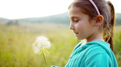 Happy Caucasian American girl blowing dandelion in meadow on Summer vacation - stock footage