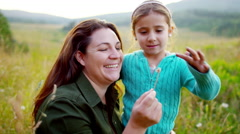 Happy Caucasian American mother and daughter blowing dandelion in meadow outdoor - stock footage