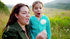 Loving Caucasian American mum and daughter blowing dandelion in field on holiday - stock footage