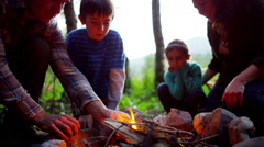 Happy American Caucasian family making campfire in woodland on holiday outdoors - stock footage