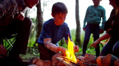 Happy American Caucasian family making campfire in woodland on holiday outdoor - stock footage