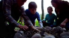 Happy American Caucasian family making campfire in forest on holiday outdoors - stock footage