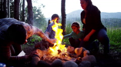 Happy American Caucasian family making campfire on Summer vacation outdoors - stock footage