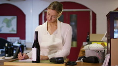 4K Portrait of friendly shopkeeper standing behind counter in wine shop - stock footage