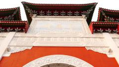 Two guards in Shrine paifang arch, tilt up to gold hieroglyph sign at roof gable - stock footage