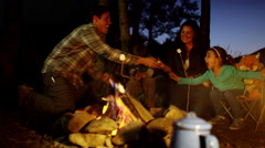 Happy American Caucasian parent and children enjoying toasting smores outdoors - stock footage