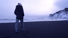 Woman walking along black beach of Iceland. Full HD Video Stock Footage